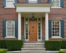 Front Of Elegantly Landscaped House With Stone Steps And Portico Over Wooden Front Door