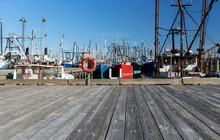 Bright Orange Life Buoy On Dock At Commercial Fishing Harbor Dock