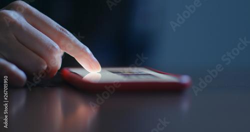 Fototapeta  Finger touch on cellphone at night