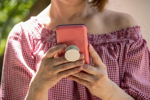 Fotografie, Obraz Close-up of woman holding and reading from a cell phone in pink case with grip h