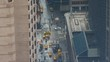 CLOSE UP: Scenic shot from above of busy roads in New York on a gray rainy day. Yellow taxi cabs line up by a traffic light in front of an intersection as pedestrians cross the street in Manhattan.