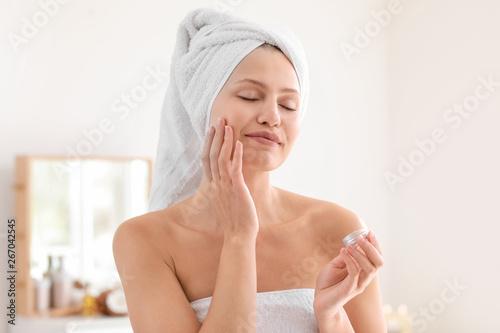 Fototapeta Beautiful young woman applying cream at home obraz na płótnie