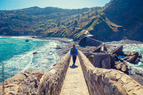 A man walks over the bridge to the island of Gaztelugatxe. Bay of Biscay, Basque Country, Spain, Europe