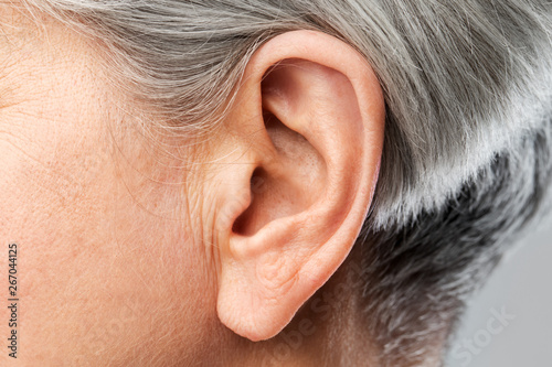 Fényképezés  hearing, body part and old age concept - close up of senior woman ear
