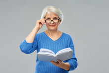 Vision, Wisdom And Old People Concept - Smiling Senior Woman In Glasses Reading Book Over Grey Background