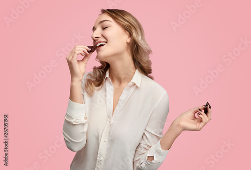 Obraz Young woman eating chocolate with closed eyes - fototapety do salonu