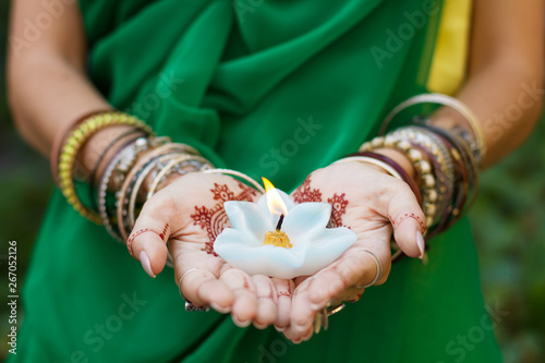 Beautiful woman in traditional Muslim Indian wedding green sari dress hands with henna tattoo mehndi pattern jewelry and bracelets hold burning lotus candle Summer culture festival celebration concept