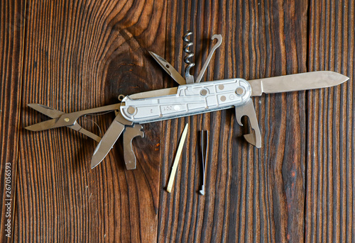 Valokuva  Multi-function knife on wooden background close - up