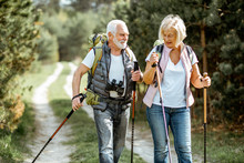Happy Senior Couple Hiking With Trekking Sticks And Backpacks At The Young Pine Forest. Enjoying Nature, Having A Good Time On Their Retirement
