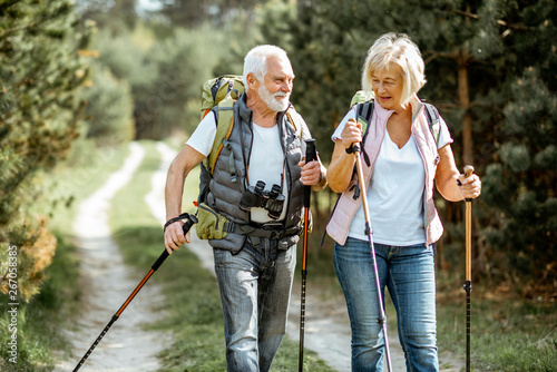 Fotografiet  Happy senior couple hiking with trekking sticks and backpacks at the young pine forest