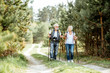 canvas print picture - Happy senior couple hiking with trekking sticks and backpacks at the young pine forest. Enjoying nature, having a good time on their retirement