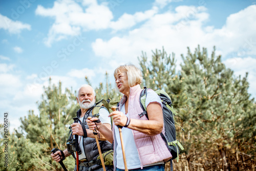 Foto auf Leinwand Olivgrun Happy senior couple hiking with trekking sticks and backpacks at the young pine forest. Enjoying nature, having a good time on their retirement