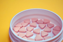 Pink Triangular Unusual Pills In A White Round Box On Yellow Background With Copyspace, Side View Closeup