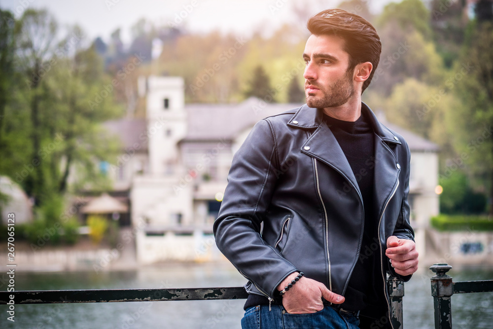 Fototapety, obrazy: One handsome young man in urban setting in modern city, standing, wearing black leather jacket and jeans, looking away