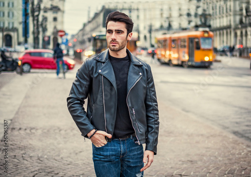 256ff072 One handsome young man in urban setting in modern city, standing, wearing  black leather