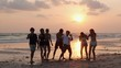 Silhouette of Asian teen group dancing and drinking beverage together in beach summer with sunset background. Young asia happy emotion and anniversary celebration. 4K resolution and slow motion.