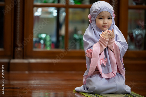 Fotografia, Obraz Muslim kid girl wearing Hijab praying Dua during Ramadan period