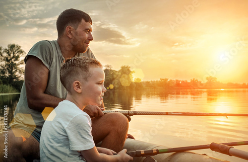 Obraz Happy Father and Son together fishing from a boat at sunset time - fototapety do salonu