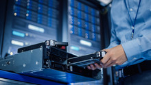 In The Modern Data Center: IT Engineer Installs New HDD Hard Drive And Other Hardware Into Server Rack Equipment. IT Specialist Doing Maintenance, Running Diagnostics And Updating Hardware.
