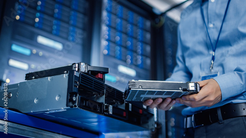 Obraz In the Modern Data Center: IT Engineer is Holding New HDD Hard Drive Prepared for Installing Hardware Equipment into Server Rack. IT Specialist Doing Maintenance and Updating Hardware. - fototapety do salonu