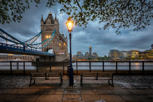 Moody View To The Tower Bridge Of London, UK, On A Rainy Spring Evening With Benches And Streetlight