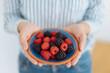 Leinwandbild Motiv Woman holding a plate of fresh mixed berries