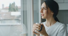 Portrait Of A Pensive Young Woman Is Drinking A Tea And Looking Through The Window In The Morning In The Kitchen.