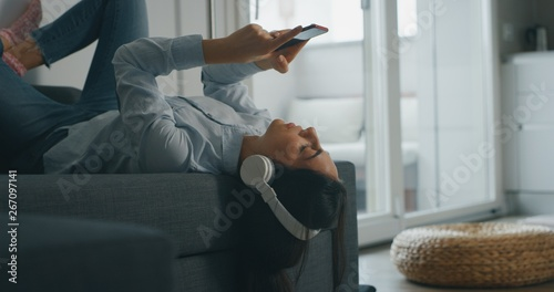 Portrait of  of an young woman is lying on the sofa is using a smart phone for listening to the music with wireless headphones in living room. - 267097141