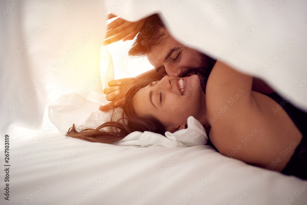 Fototapeta Happy couple having fun in bed.