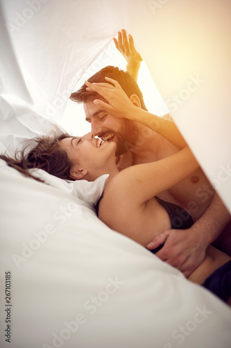 Couple in love having intimate sex in bed.