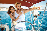 Beautiful couple of lovers sailing on a boat and enjoy bright sunny day.