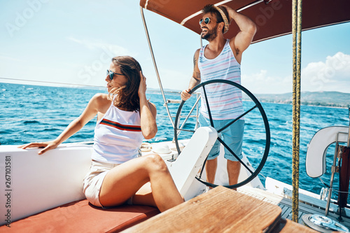 Poster de jardin Individuel Young man and woman on a sailing boat -Romantic vacation and luxury travel..