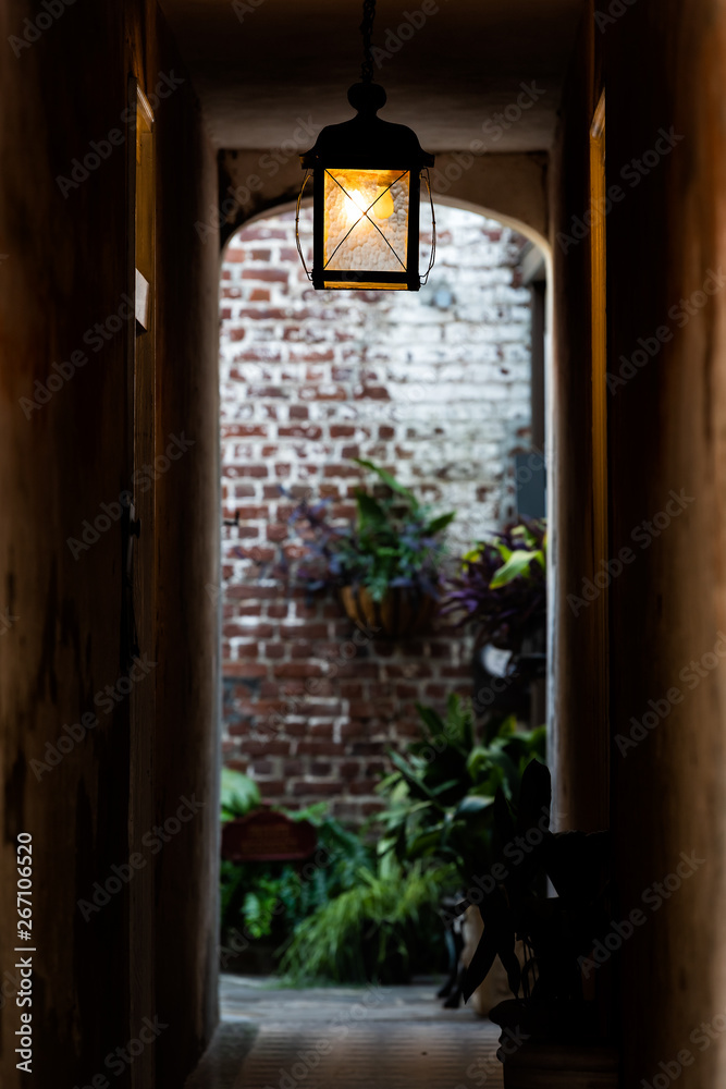 Nobody in old vintage stone brick architecture and narrow dark alley vertical view with illuminated lantern lsmp in passage tunnel