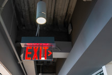 Red Exit Sign Hanging From Ceiling Looking Up View With Arrow Direction And Color Illuminated Fixture In Office Building Emergency Closeup