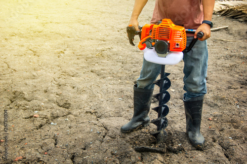 Fotografie, Obraz farmer using tools hand-held soil hole drilling machine or portable manual earth auger for prepare the soil for planting trees with soil mold background organic farming and copy space