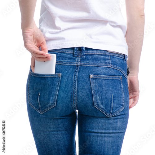 Fotografia Woman puts mobile phone in jeans pocket on white background