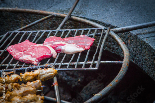 Photo  Chicken legs and raw steaks on a grill grill over the natural heat of a volcano in El Diablo Canary Islands National Park