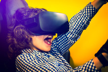 Excited Little Kid Using Virtual Reality Glasses. Selective Focus. Close-up. Happy Young Man Is Playing Racing Videogame In 3D Virtual Reality Simulator Using Headset. Driving Car In Virtual Reality.