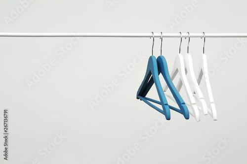 фотографія  Empty clothes hangers on metal rail against light background