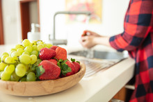 Wooden Bowl With Green Grapes And Strawberries In The Kitchen And A Woman Rinses Fruits On The Background.