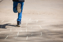 Child Boy Plays Hopscotch On Asphalt. A Child Plays Hopscotch On A Playground In A Park Outside On A Sunny Day. Early Development. Outdoor Activities For Children.