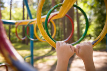 Young Boy Climbing On The Playground During The Summer. The Child Likes To Climb The Monkey Bar On The Playground In The Fresh Air. Little Boy Hands
