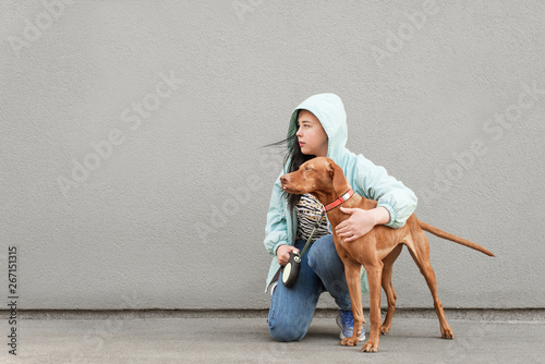Woman holds a dog on a leash, sits on the background of a
