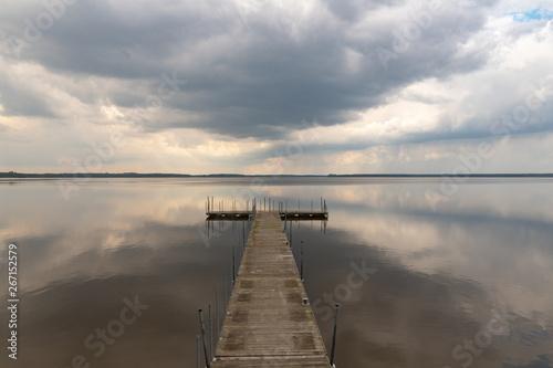 Fototapeta A small bridge over the lake. Reflection of clouds on the lake's surface. obraz na płótnie
