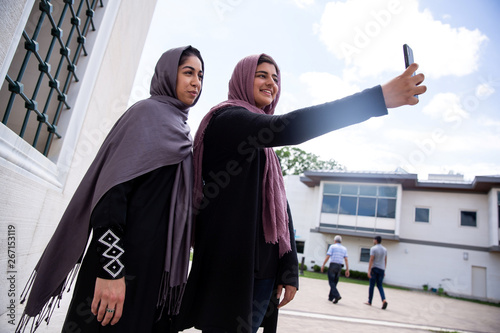 Two Muslim women take pictures after the first Friday prayers during the month of Ramadan at