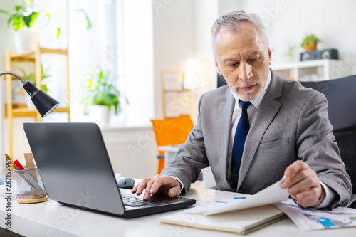 Focused good-looking senior man with stubble checking documents