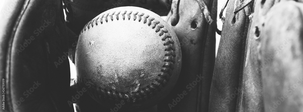 Fototapeta Close up of old vintage baseball in used worn leather glove, black and white sports banner.