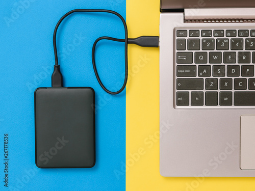 Black hard drive and laptop on yellow and blue background. Flat lay. The concept of backup storage. - fototapety na wymiar