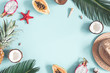 Leinwandbild Motiv Summer composition. Tropical palm leaves, hat, fruits on blue background. Summer concept. Flat lay, top view, copy space
