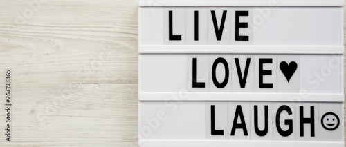 """Live Love Laugh' words on lightbox over white wooden surface, overhead view Canvas Print"